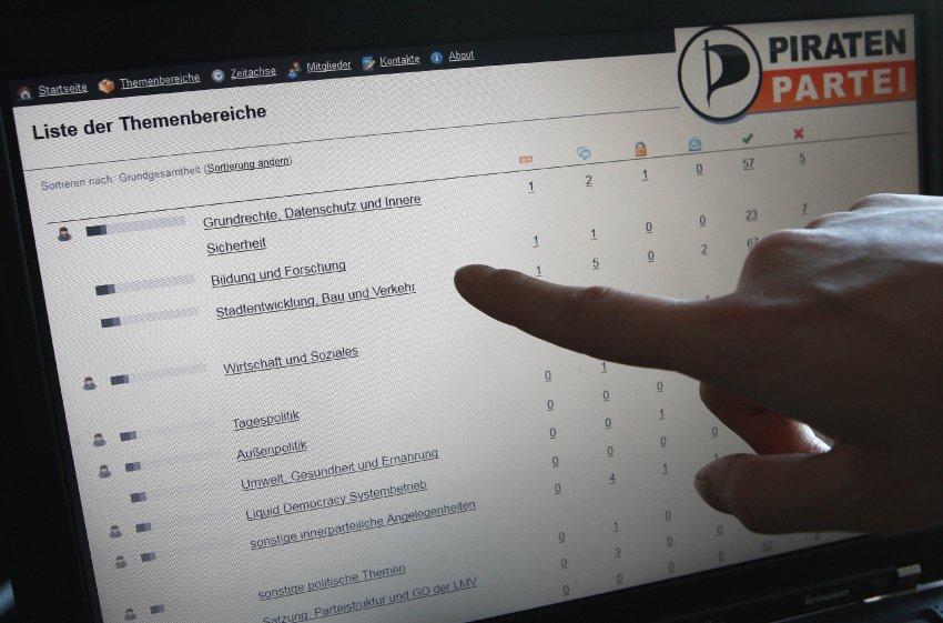 """Berlin/ Ein Mitglied der Piratenpartei zeigt am Sonntag (20.05.12) in Berlin auf dem zweiten Liquid Feedback (LQFB) Thementag der Piratenpartei Berlin auf einem Laptop, auf dessen Monitor eine Seite der Software Liquid Feedback unter einem Logo der Piratenpartei zu sehen ist. Liquid Feedback ist eine Software, die von Mitgliedern der Piratenpartei entwickelt wurde, um deren Demokratiekonzept der Liquid Democracy (""""Fluessige Demokratie"""") umzusetzen. Foto: Adam Berry/dapd"""
